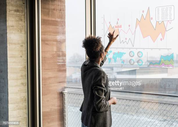 young woman touching windowpane with graph in office - berühren stock-fotos und bilder