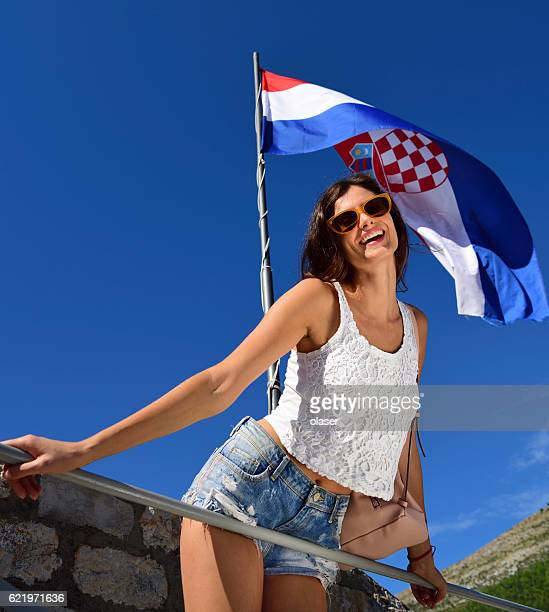 Young woman tourist Dubrovnik, wall, and flag in background