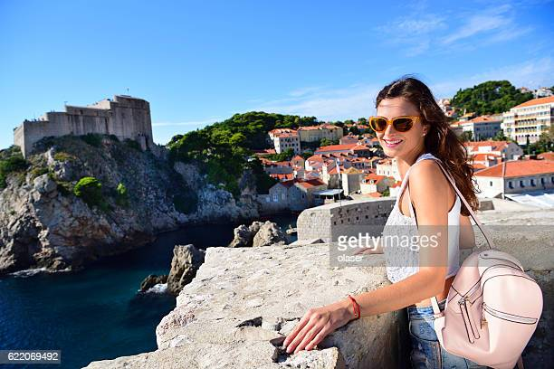 Young woman tourist Dubrovnik, wall, rooftops, old town in background