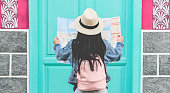 Young woman tourist looking map during city tour - Travel girl going around old town on vacation - Holiday, wanderlust and trip trends concept - Focus on hat