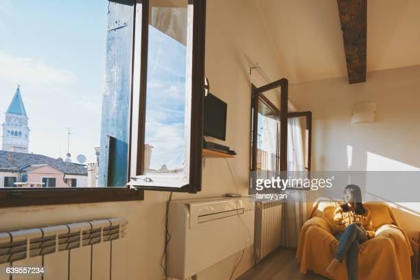 Young woman tourist sitting on sofa in airbnb