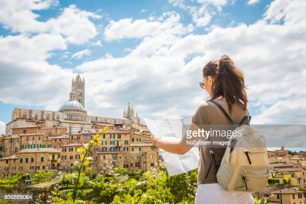 young woman tourist with map in siena. - siena italy stock photos and pictures