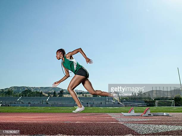 young woman track athlete starting from blocks - running track stock pictures, royalty-free photos & images