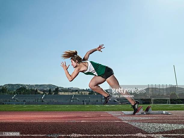 Young woman track athlete starting from blocks