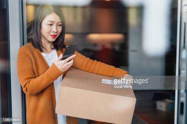 young woman tracking home delivery on smart phone - portable information device stock pictures, royalty-free photos & images