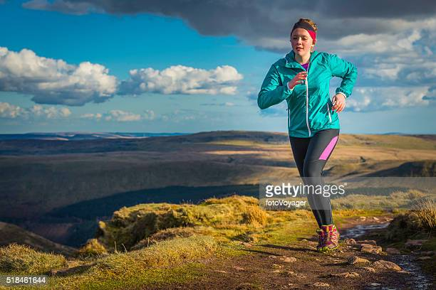 Young woman trail running along wilderness path on mountain top