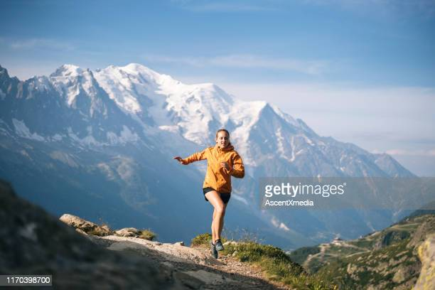 young woman trail runs in mountains - forward athlete stock pictures, royalty-free photos & images