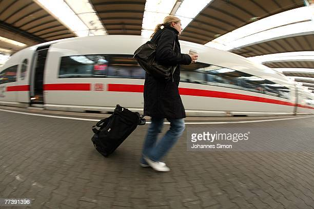 A young woman trailing a trolley passes an ICE train at Hauptbahnhof Main Station on October 18 2007 in Munich Germany Due to a new strike of the...