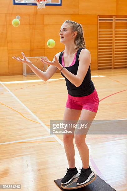 Young Woman Training Body Coordination and Equilibrium in the Gym