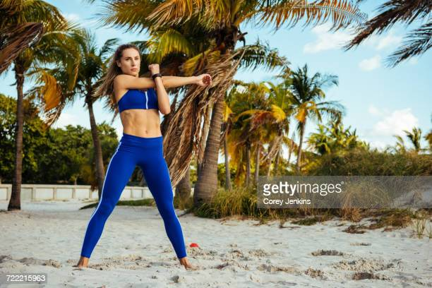 Young woman training, crossing and stretching arms at beach
