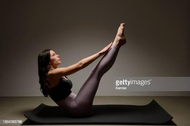 junge frau trainiert ihre bauchmuskeln - kemter stock-fotos und bilder