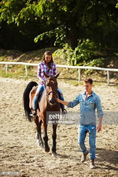Young woman training horseback riding technique with instructor.