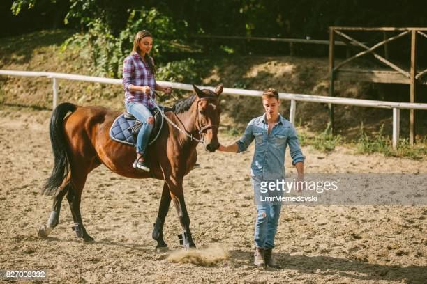 若い女性トレーニング乗馬技術インストラクターと一緒に。 - 手綱 ストックフォトと画像