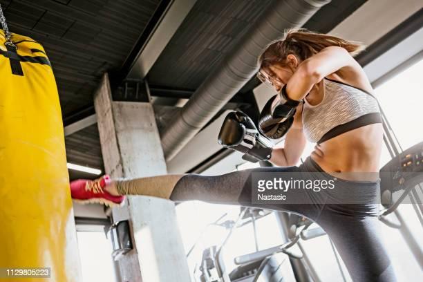 kickboxing de formation de jeune femme, poinçon de high-kick - donner un coup de pied photos et images de collection