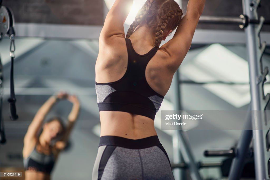 Young woman training, looking in mirror while stretching arms in gym : Stock Photo