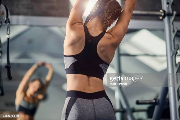 Young woman training, looking in mirror while stretching arms in gym