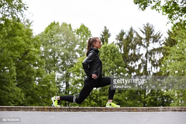 young woman training, lunging on top of wall - flexionando perna - fotografias e filmes do acervo
