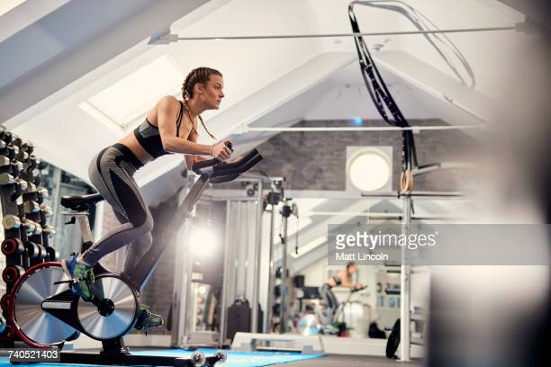 young woman training, pedalling exercise bike in gym - peloton stock pictures, royalty-free photos & images