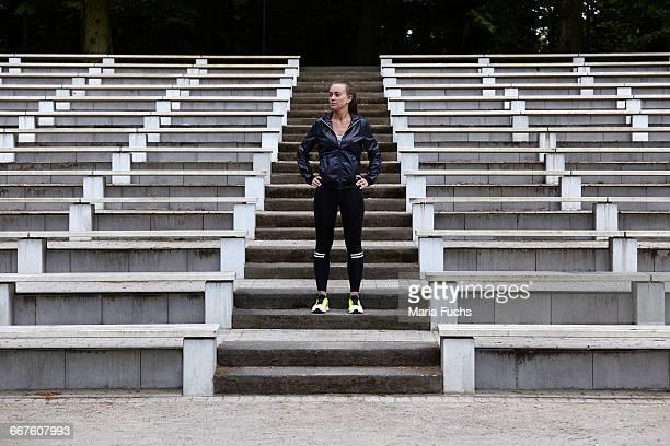 Young woman training, preparing to run on stadium stairway