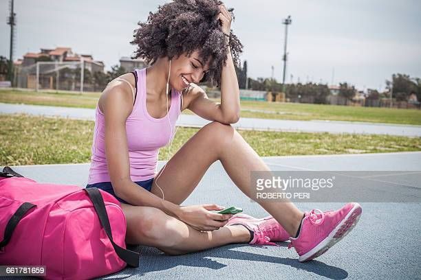 young woman training, taking a break on running track - gym bag stock pictures, royalty-free photos & images