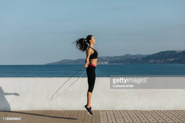 young woman training with a jumping rope - skipping along stock photos and pictures