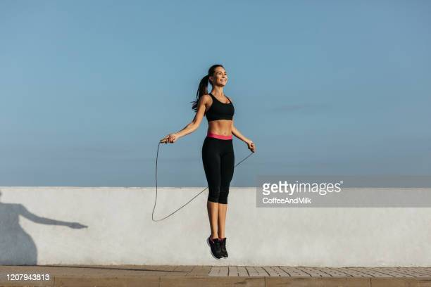 young woman training with a jumping rope - skipping along stock pictures, royalty-free photos & images