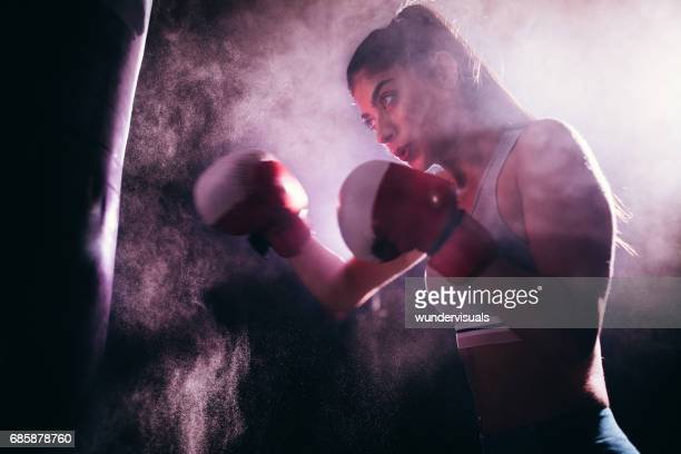 young woman training with boxing gloves and a punching bag - muay thai imagens e fotografias de stock