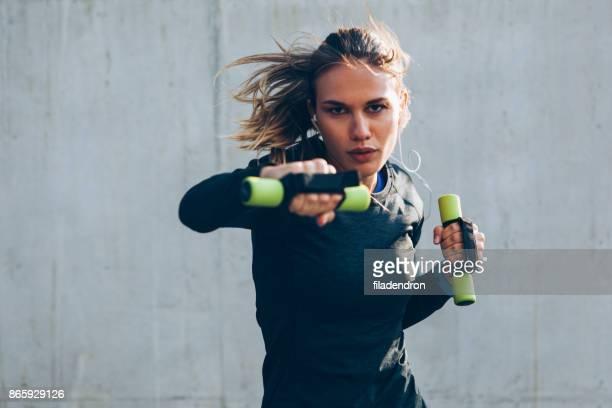junge frau, die training mit kurzhanteln - muskel stock-fotos und bilder