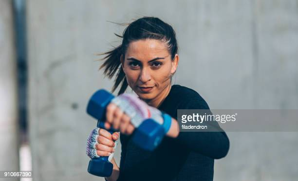 young woman training with dumbbells - sportsperson stock pictures, royalty-free photos & images