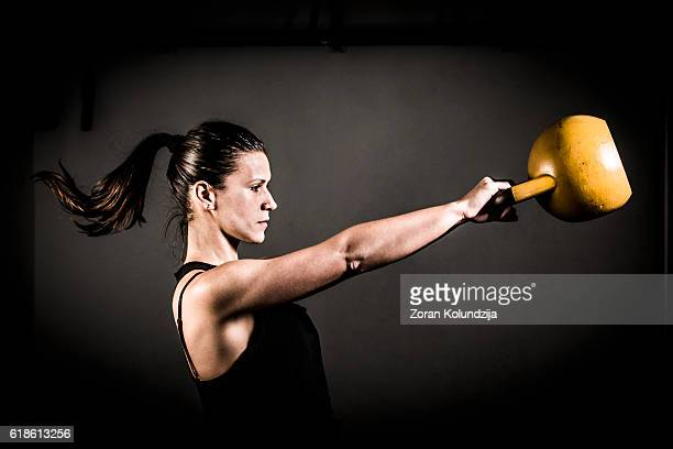 Young woman training with kettlebell in gym