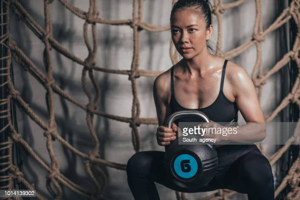 young woman training with kettlebell - one young woman only stock pictures, royalty-free photos & images