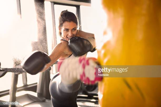 young woman training with punching bag - kickboxing stock pictures, royalty-free photos & images