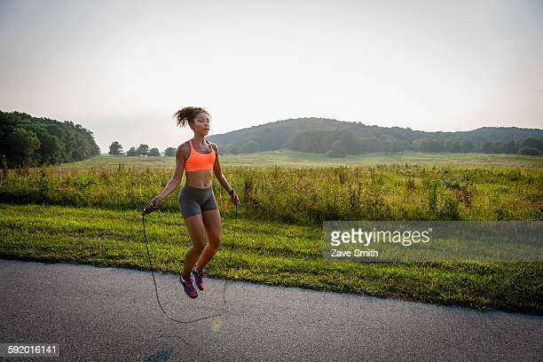 Young woman training with skipping rope in rural park