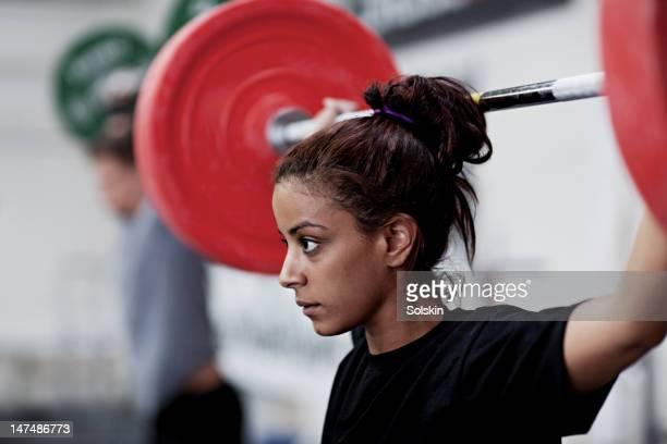 young woman training with weights - weight training stock pictures, royalty-free photos & images
