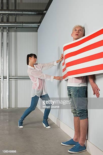 Junge Frau speichern junger Mann hinter gestreifte Tapete