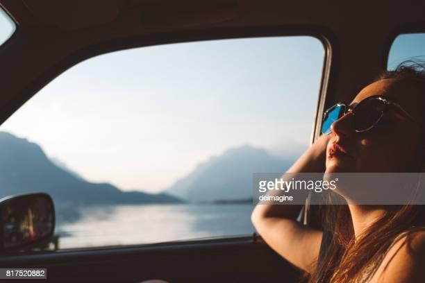 jonge vrouw reizen met de auto in de buurt van road lake panoramisch - landvoertuig stockfoto's en -beelden