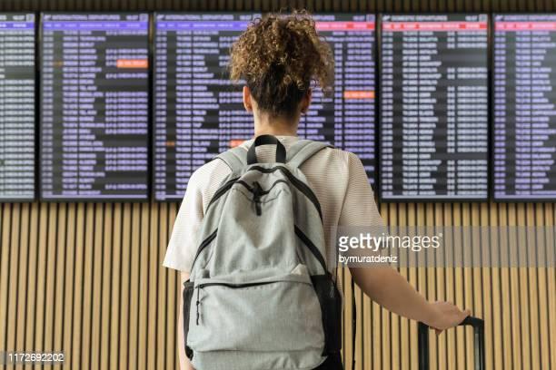 joven viajera mirando información de vuelo - cambio horario fotografías e imágenes de stock