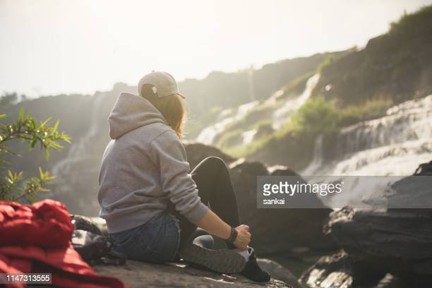 young woman traveler outdoors - behind waterfall stock pictures, royalty-free photos & images