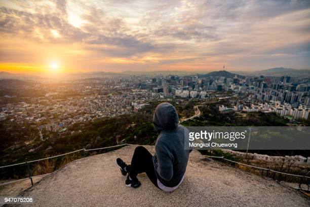 young woman traveler sitting on the rock looking sunrise scene of seoul downtown city skyline, view of n seoul tower at namsan park in best viewpoint from inwangsan mountain in seoul city, south korea - anhöhe stock-fotos und bilder