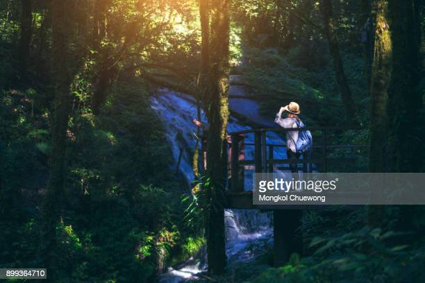 Young woman traveler travelling into beautiful waterfalls at the peak of mountian in kew mae pan nature trail at Doi Inthanon National Park, Chiang Mai Province, Thailand