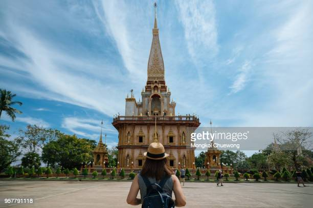 young woman traveler with backpack traveling into beautiful pagoda in wat chalong or chalong temple at phuket town, thailand. it's most popular thai temple in phuket thailand. - place of worship stock pictures, royalty-free photos & images