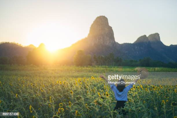 Young woman traveler with hat in sunflower fields with happiness and cheerful at sunset and arms raised up.