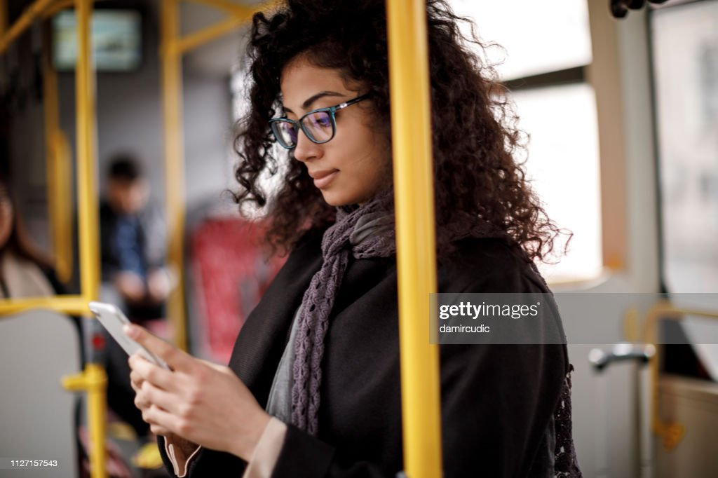 Young woman traveling by bus and using smart phone : Stock Photo