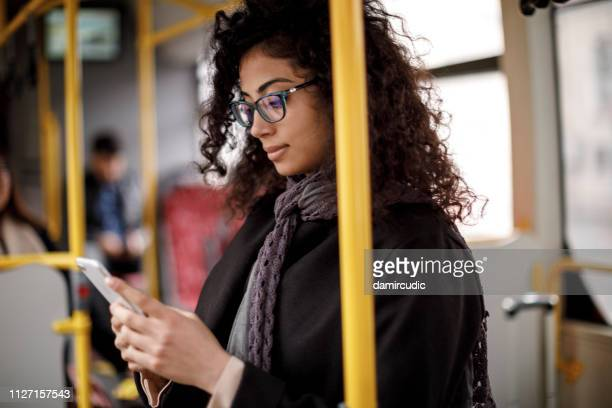 young woman traveling by bus and using smart phone - rush hour stock pictures, royalty-free photos & images