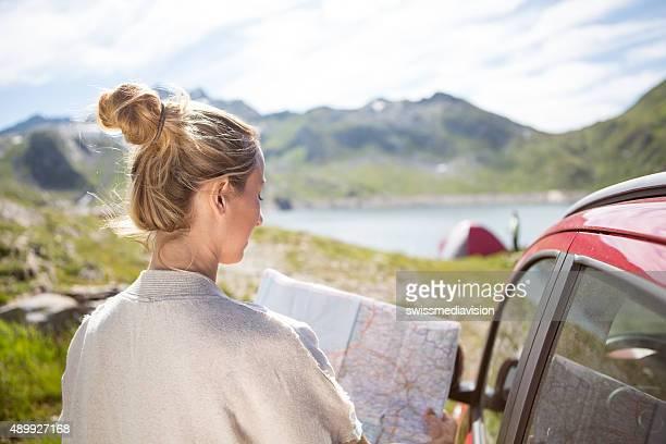 Junge Frau, die mit dem Auto anreisen, lesen Sie Karte-Natur