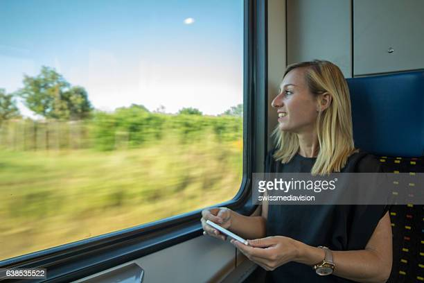 Young woman traveling by train, holding mobile phone