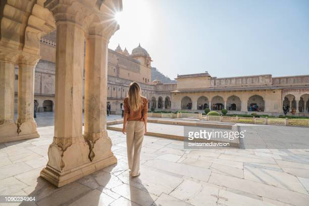 young woman traveling in india contemplating ancient temple in jaipur, india - amber fort stock pictures, royalty-free photos & images