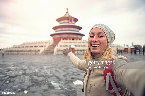 Young woman traveling takes selfie with Temple of Heaven,Beijing