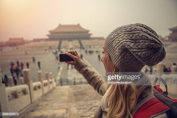 Young woman traveling takes smart phone picture of Forbidden City