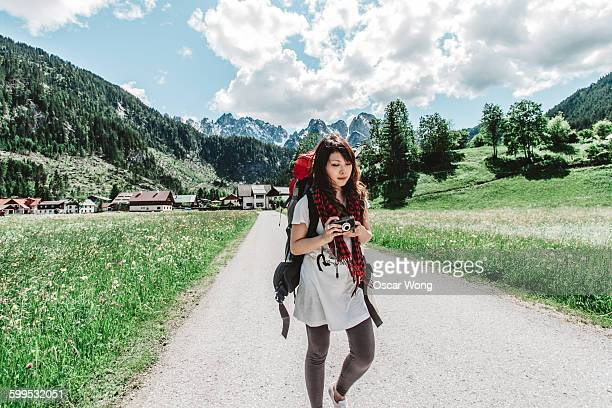 Young woman traveling with backpack and camera